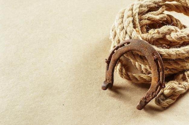Antigua herradura y cuerda en tablas de madera.