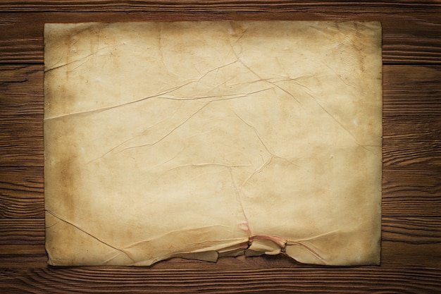 Antigua hoja de papel horizontal roto en tablero de madera marrón