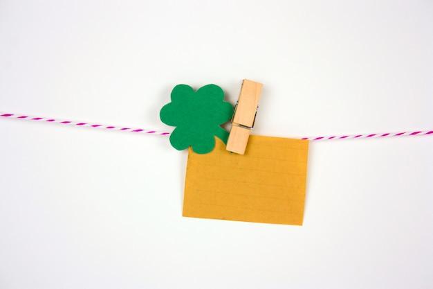 Antigua maqueta de papel vintage y hojas de corte de papel de trébol en pinza para la ropa en bakground blanco