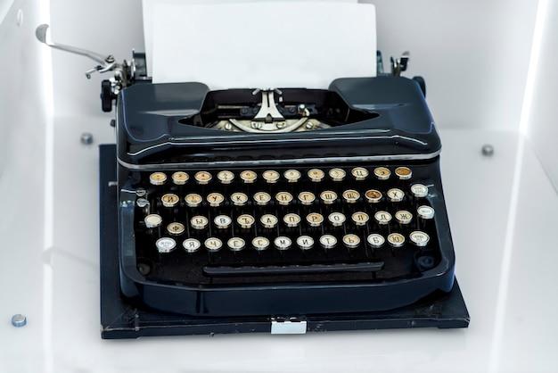 Antigua máquina de escribir vintage con una hoja de papel en blanco insertada