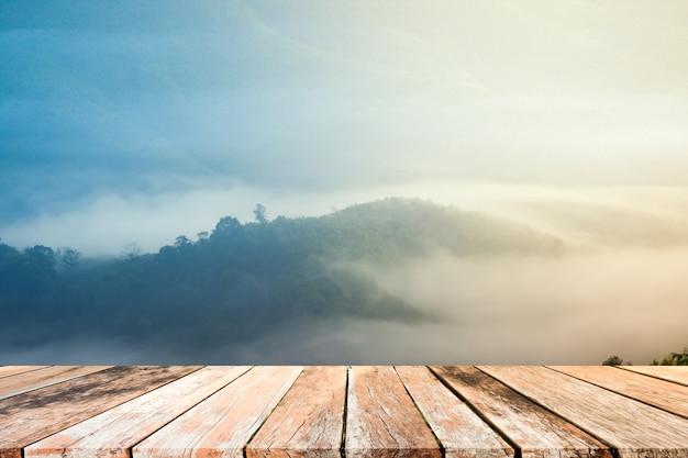 Antigua mesa de madera en blanco con montañas y niebla