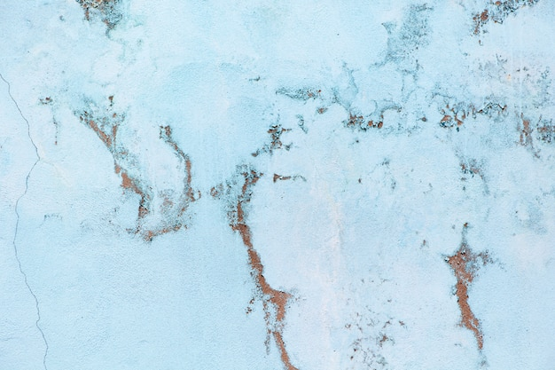 Antigua muralla azul pastel con abrasiones.