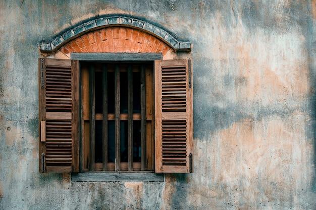 Antigua muralla de cemento con ventana de madera.