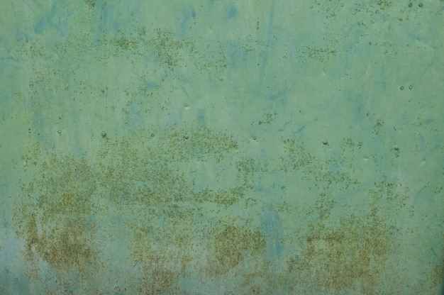 Antigua muralla de metal naranja en verde