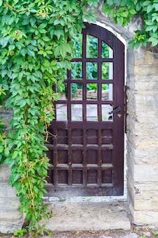 Antigua puerta de acceso metálica a la casa con hiedra colgada en la fachada.