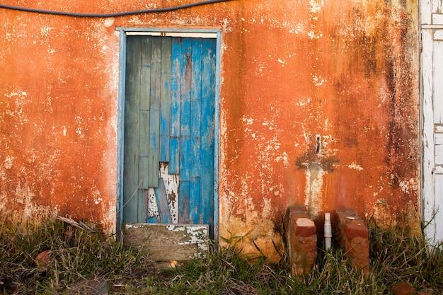 Antigua puerta de color azul en casa abandonada en campo