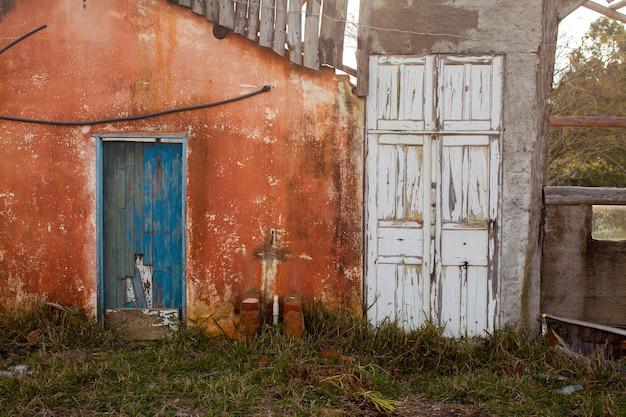 Antigua puerta de color en casa abandonada en campo