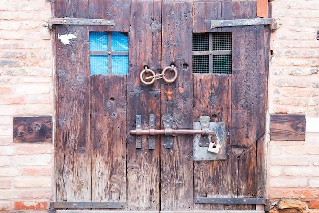 Antigua puerta doble de madera antigua con cerraduras antiguas y una manija en las calles de bérgamo, italia