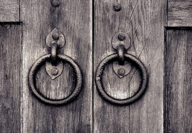 Antigua puerta de madera con dos aldabas de puerta.