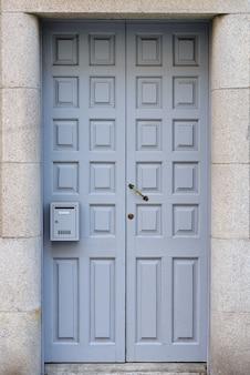 Antigua puerta de madera gris con buzón de cerca
