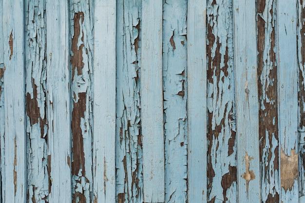 Antigua puerta de madera con pintura descascarada y agrietada blanca y azul.