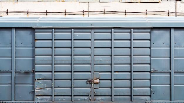 Antigua puerta de metal con un gran candado en un almacén, garaje.