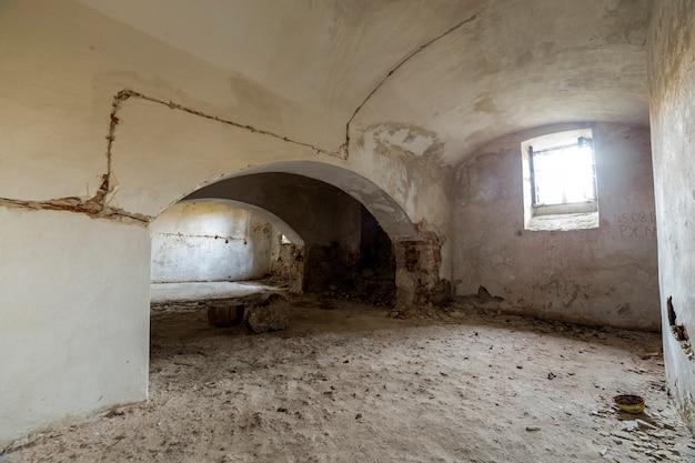 Antigua sala de sótano vacía abandonada del antiguo edificio o palacio con paredes de ladrillo enlucidas, techo bajo arqueado, pequeñas ventanas con rejas de hierro y suelo sucio.