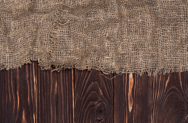 Antigua servilleta de tela de arpillera sobre fondo de madera marrón, vista superior
