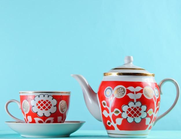 Antigua taza de cerámica y una tetera en la mesa de madera contra la pared azul
