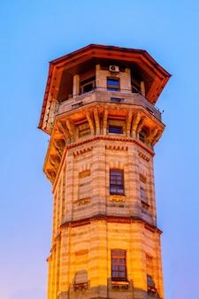 Antigua torre de agua en chisinau al anochecer. iluminación