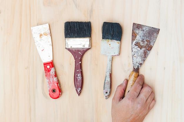 Antiguas herramientas de mano de pintura con mano sobre fondo de madera