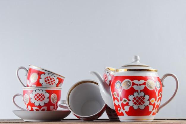 Antiguas tazas de cerámica y una tetera en la mesa de madera contra una pared blanca