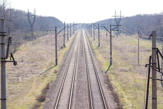 Antiguas vías de ferrocarril ligeramente oxidadas en las que todavía viajan trenes
