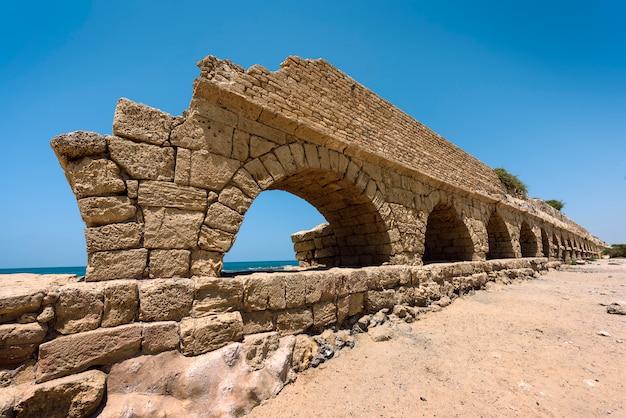 Antiguo acueducto romano en ceasarea en la costa del mar mediterráneo, israel