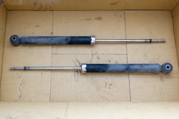 El antiguo amortiguador en la caja de la caja que se quitó de un sedán pequeño después de ser inspeccionado en el centro de servicio, vista frontal con el espacio de la copia.
