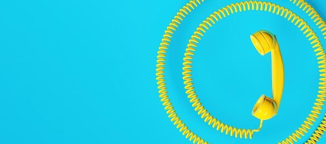 Antiguo auricular de teléfono amarillo con cable en espiral y espacio para texto