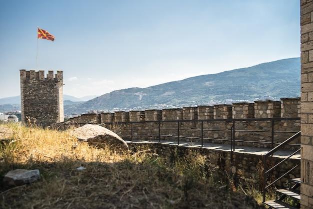 Antiguo castillo con la bandera de macedonia rodeado de colinas cubiertas de vegetación