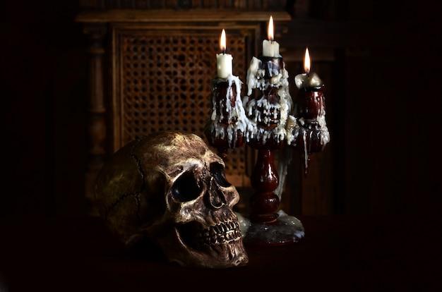 Antiguo cráneo maltratado se encuentra con un candelabro de madera antiguo