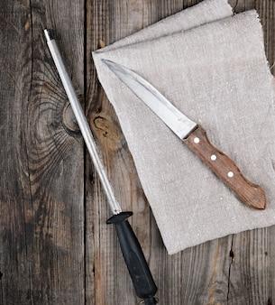 Antiguo cuchillo afilado y sacapuntas con un mango sobre un fondo de madera gris