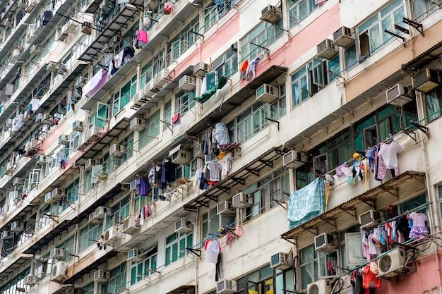 Antiguo edificio de apartamentos con ventanas envejecidas con tendedero y aire acondicionado.