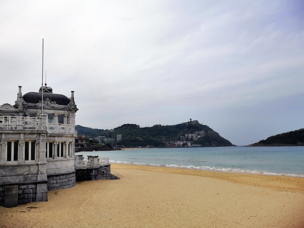 Antiguo edificio histórico a la orilla del mar en la ciudad turística de san sebastián, españa