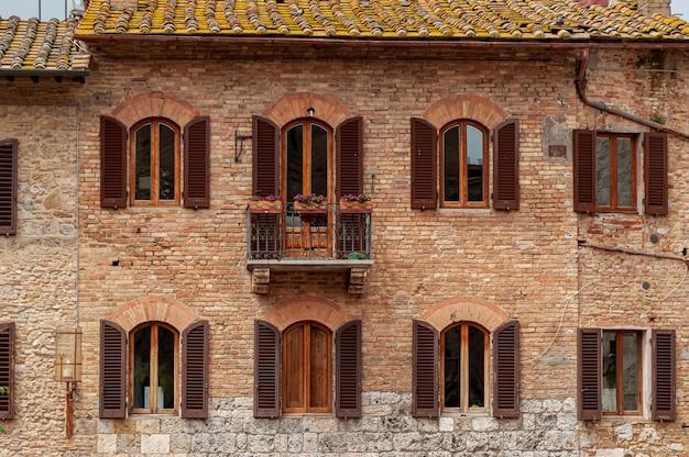 Antiguo edificio de ladrillo rojo con persianas de madera abiertas en ventanas y techo de tejas