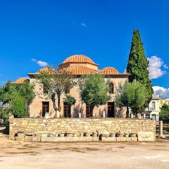 Antiguo edificio de piedra europeo con techo de tejas en el centro de atenas, grecia.