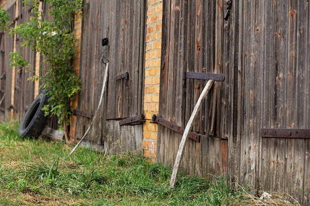 Antiguo establo. gran puerta de madera y madera seca. antiguo edificio de ladrillo