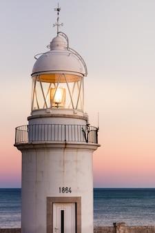 Antiguo faro en la costa con una hermosa puesta de sol de fondo