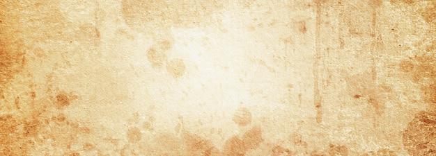 Un antiguo fondo de grunge de papel rugoso beige en manchas y rayas con un lugar para el texto