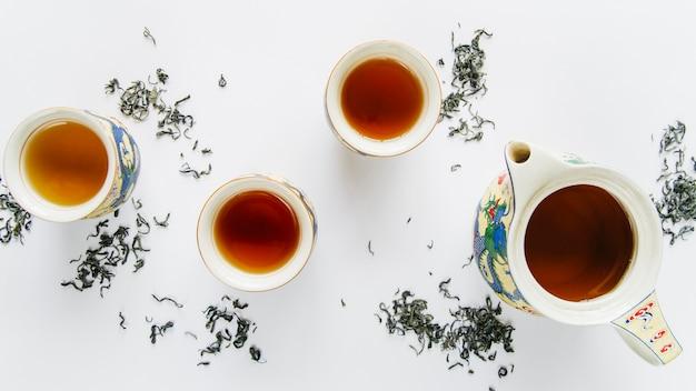 Antiguo juego de té de cerámica china con hojas secas aisladas sobre fondo blanco