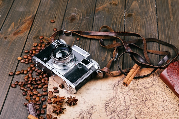 Antiguo mapa amarillo, gafas, monedas, estuche de cuero, cámara, reloj, brújulas, granos de café, otras especias y galletas se encuentran en el piso de madera