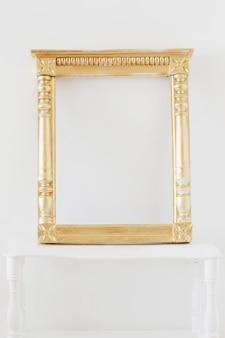Antiguo marco de madera dorada en la pared de fondo blanco