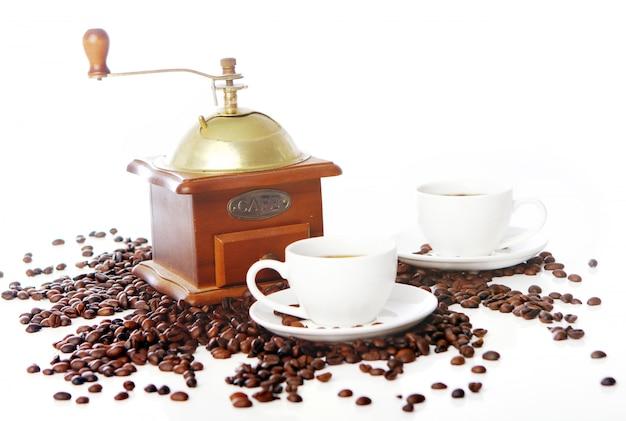 Antiguo molinillo de café con taza blanca