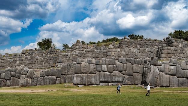 Antiguo muro de piedra y turistas cerca de él con un cielo azul