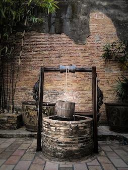 Antiguo pozo artesiano con cubo de madera colgante y techo de madera.