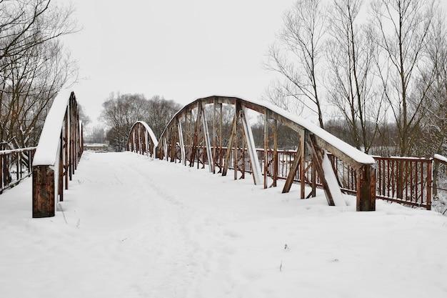 Antiguo puente de carretera de acero sobre el río después de las nevadas