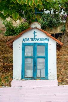 Un antiguo santuario en la calle de piedra con iconos en el interior en skala fourkas, grecia