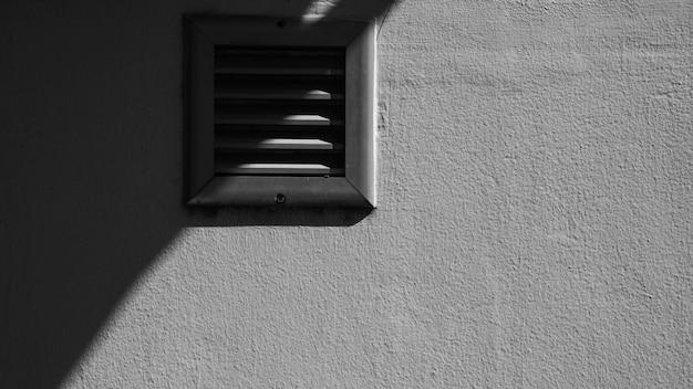 Antiguo sistema de ventilación en pared de cemento blanco.
