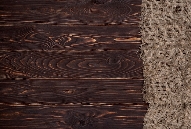 Antiguo tejido de arpillera sobre superficie de madera marrón