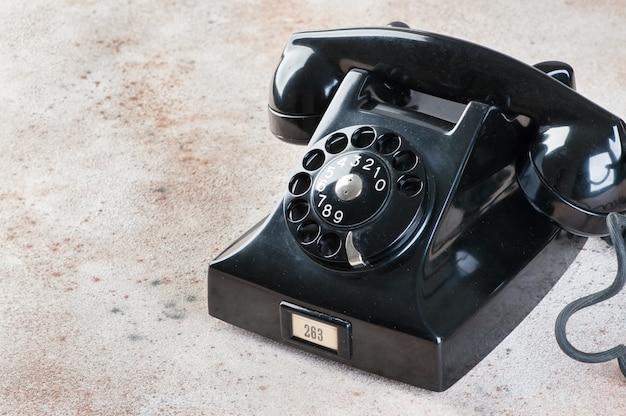Antiguo teléfono rotatorio negro sobre fondo de hormigón.