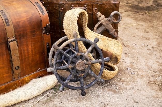 Antiguo timón de barco junto a un antiguo ancla