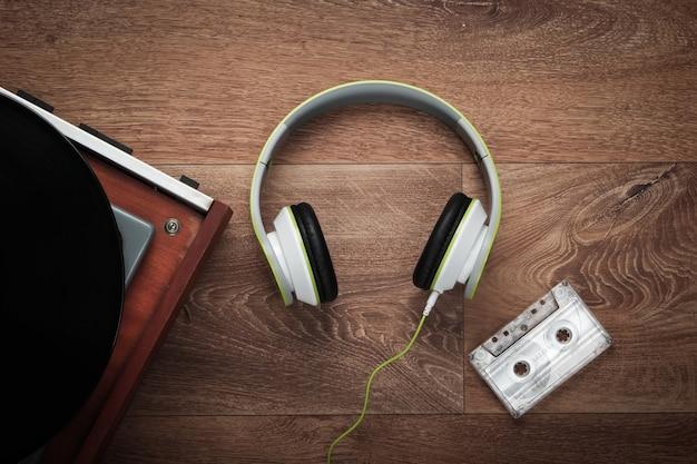 Antiguo tocadiscos de vinilo con auriculares estéreo y casetes de audio sobre un piso de madera