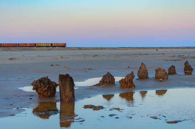 Antiguos vagones de tren oxidados con estalactitas de sal en el lago baskunchak